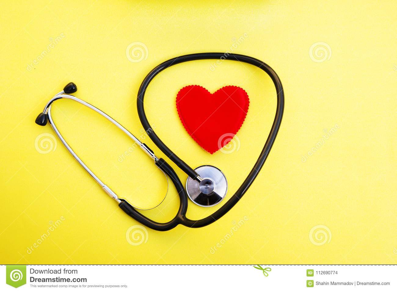 Red heart and stethoscope on yellow background, heart health care and medical technology concept, selective focus,