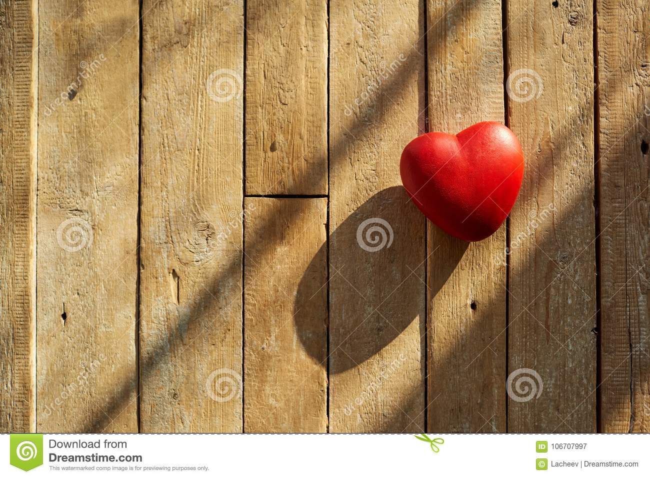 Red heart on a wooden background.