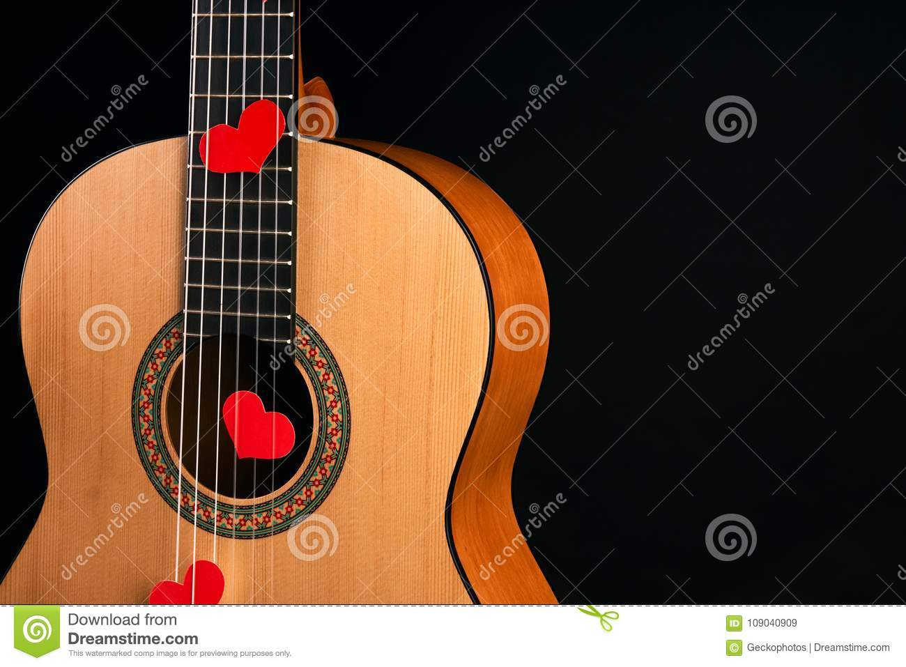 Red hearts on the strings of a guitar