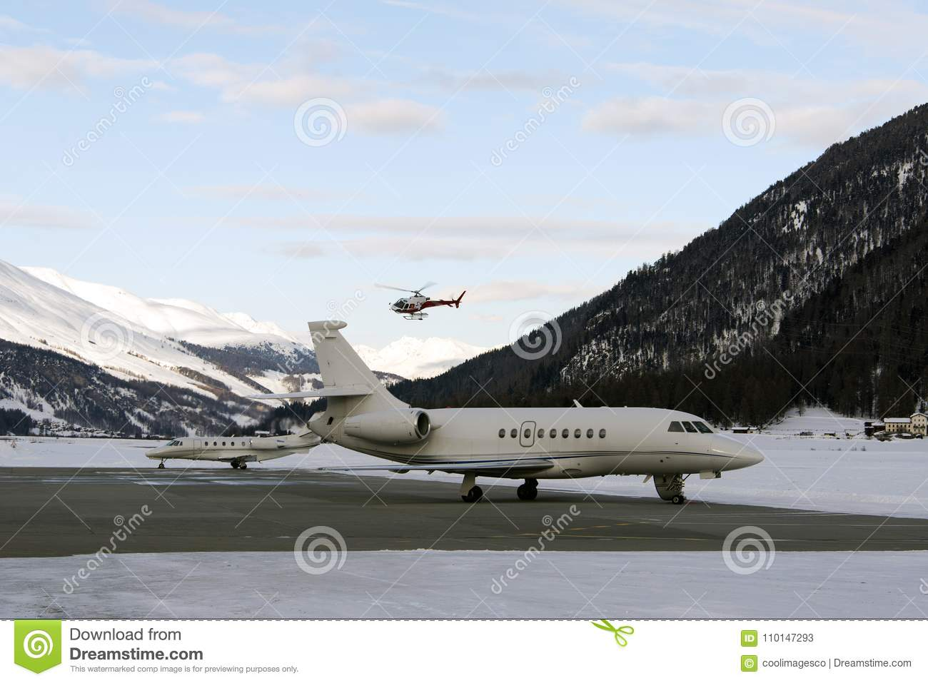A red helicopter flying over two private jets in the airport of St Moritz Switzerland in winter