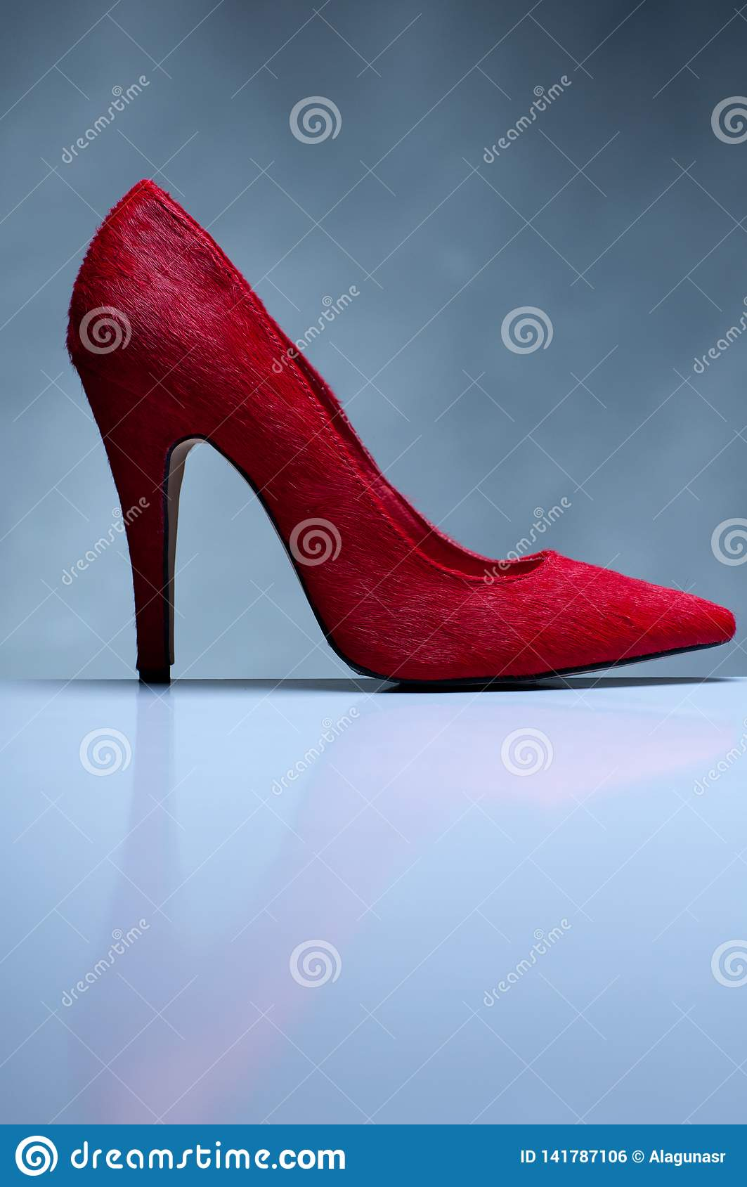 Red high heels on grey background