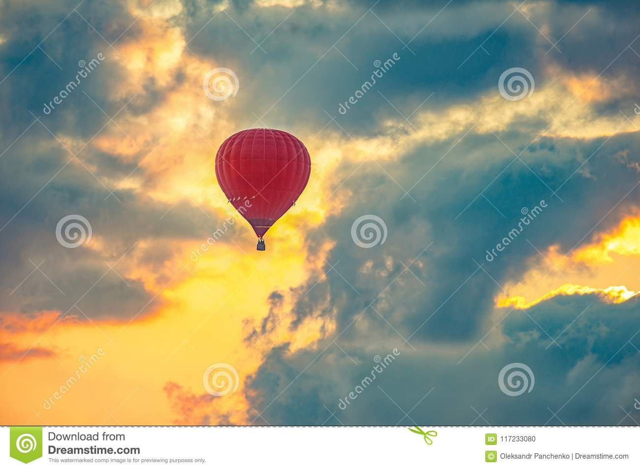 Red hot air balloon flying in beautiful sky, during sunrise.