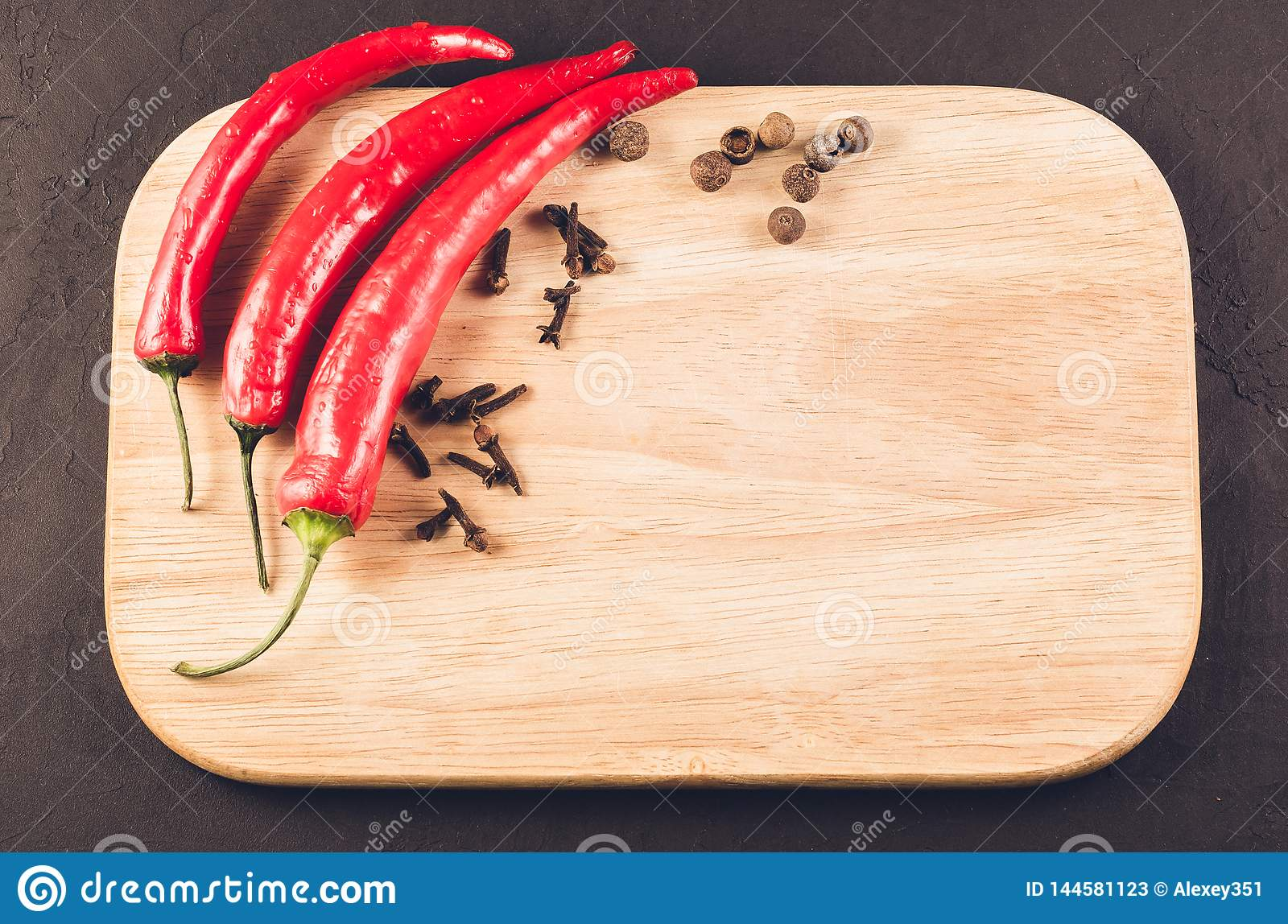 Red hot chili peppers and spices on a empty cutting board/Red hot chili peppers and spices on a empty cutting board on a dark