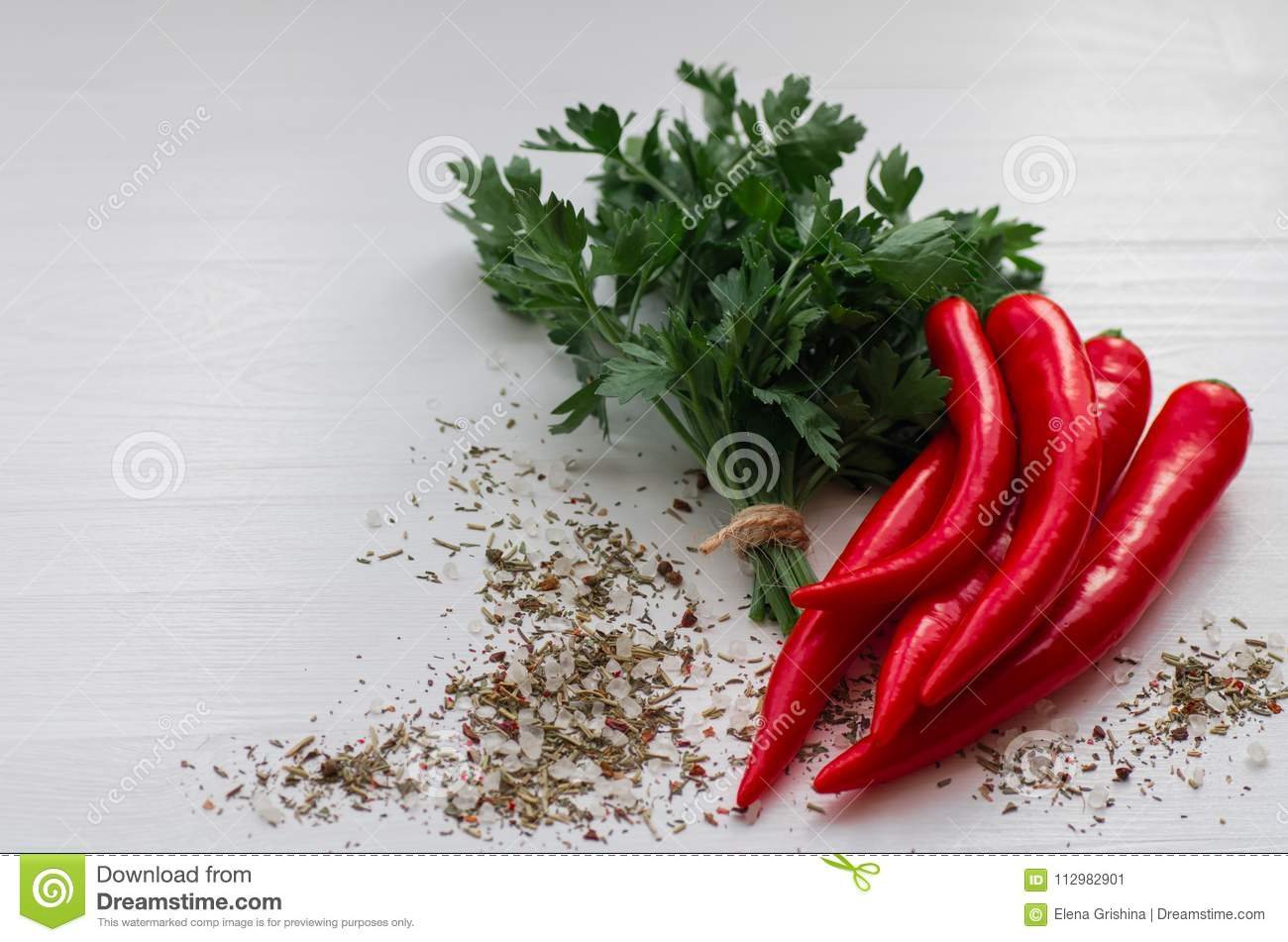 Parsley and spice leaves. Red chili peppers on white background.