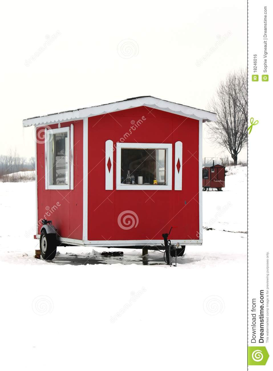 Picturesque red ice fishing cabin on river in winter.