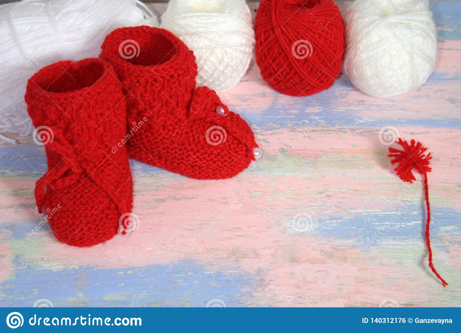 Red knitted baby booties, a red and white balls of wool yarn for knitting and a red pompon of yarn on a pink - blue background