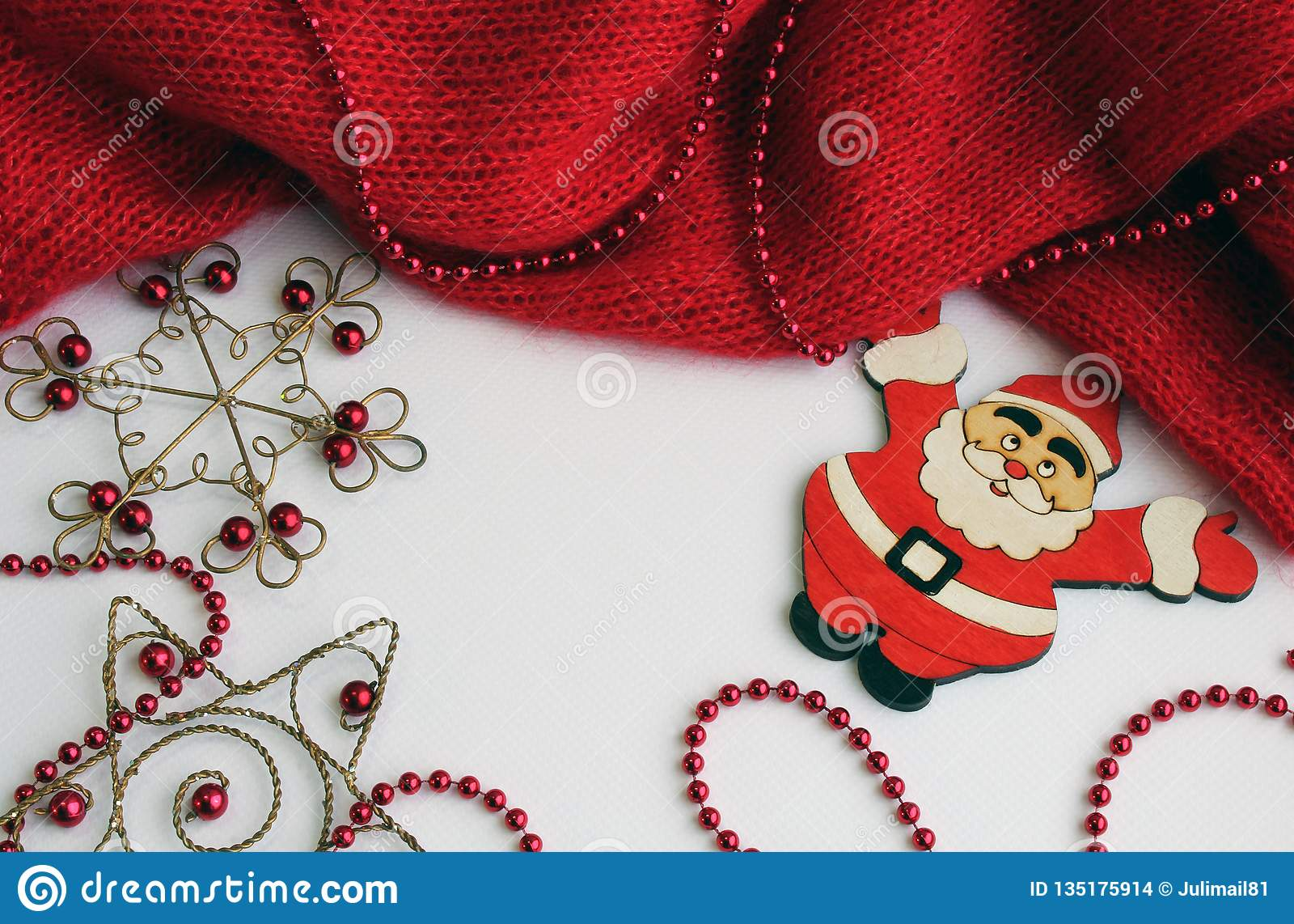 Red knitted piece on a light background with beads of red color. Nearby lies the figure of Santa Claus
