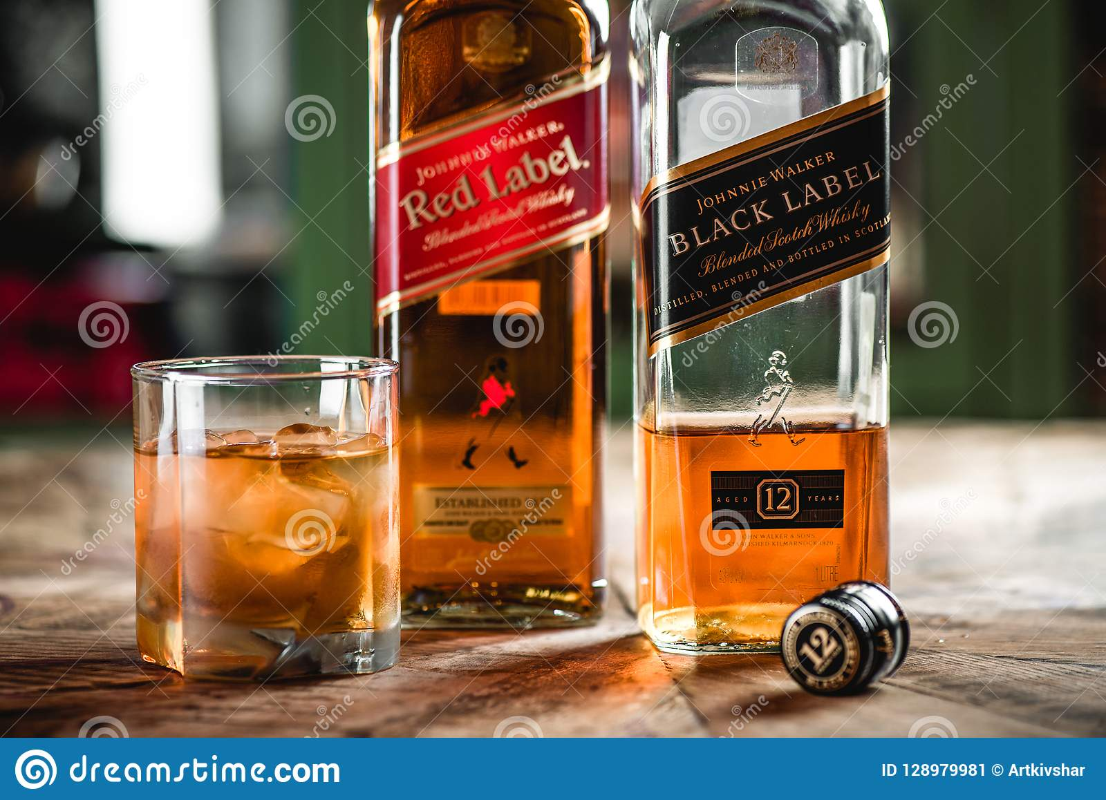 Red Label And Black Label Whiskey Bottles And Glass With Ice