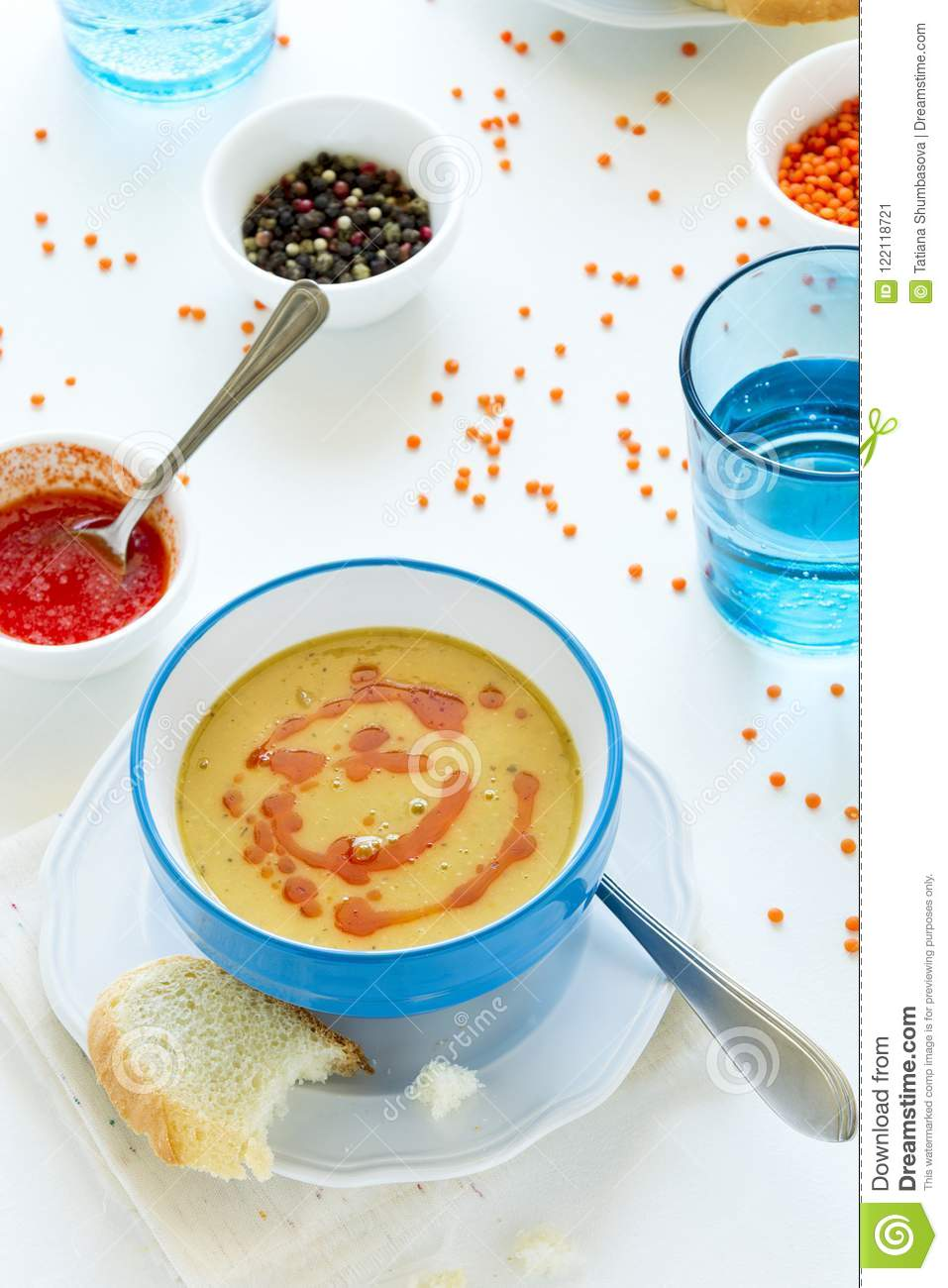 Red lentil soup with chili pepper sauce and bread on white wooden table