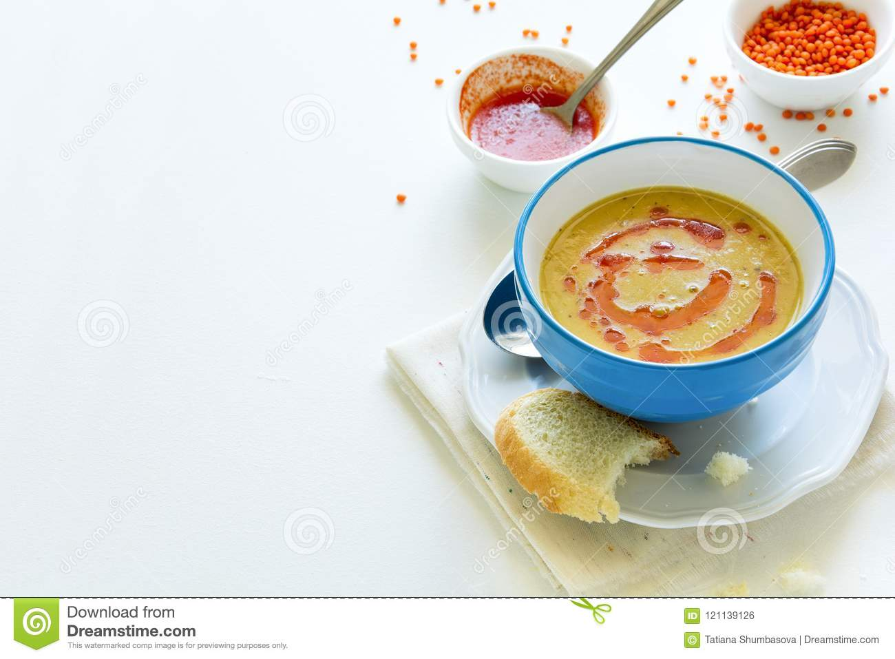 Red lentil soup with chilli pepper sauce and bread on white wooden table