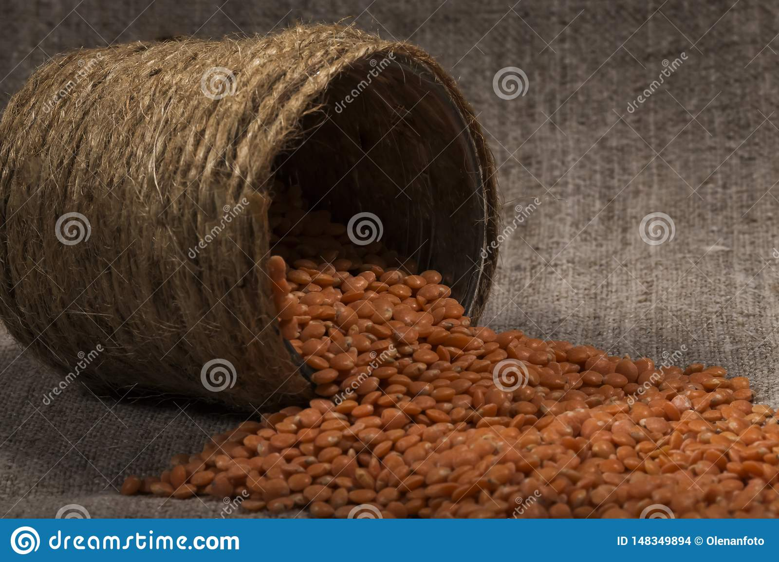 Red lentils  poured out, scatter of cans of handmade. lentil texture, lentil pattern, background, macro. concept of healthy eating
