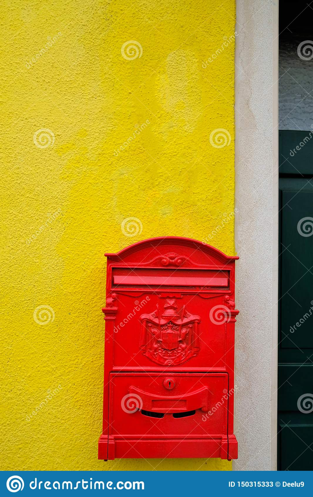 Red letter box hanging on a yellow wall