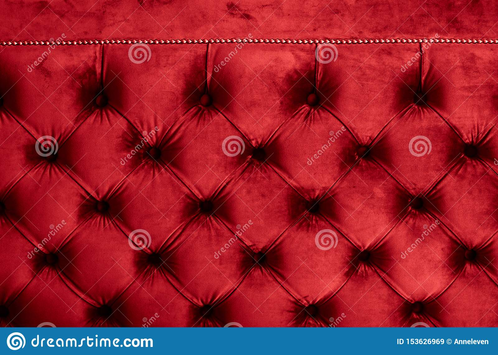 Red luxury velour quilted sofa upholstery with buttons, elegant home decor texture and background