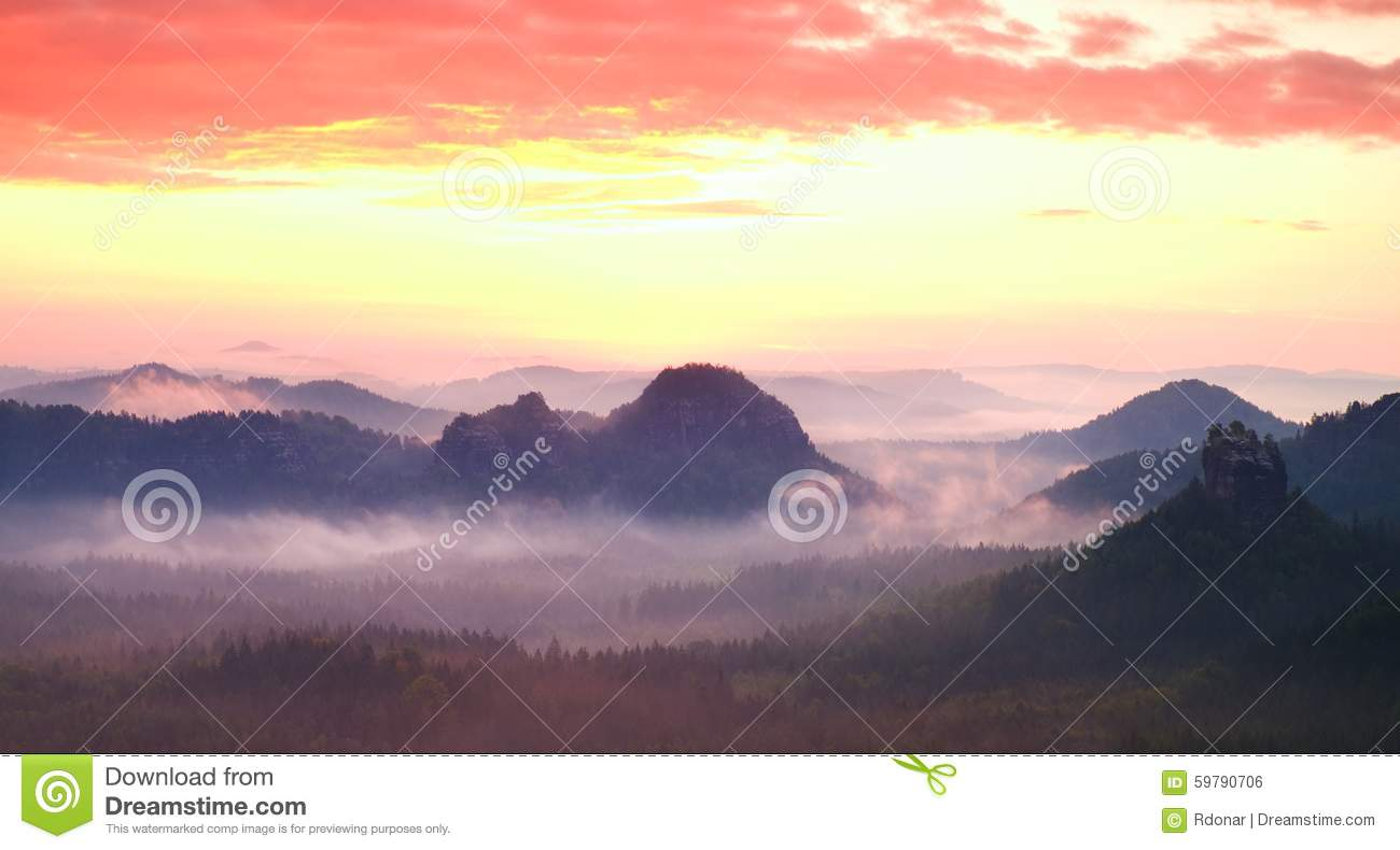 Red misty landscape panorama in mountains. Fantastic dreamy sunrise on rocky mountains. Foggy misty valley below