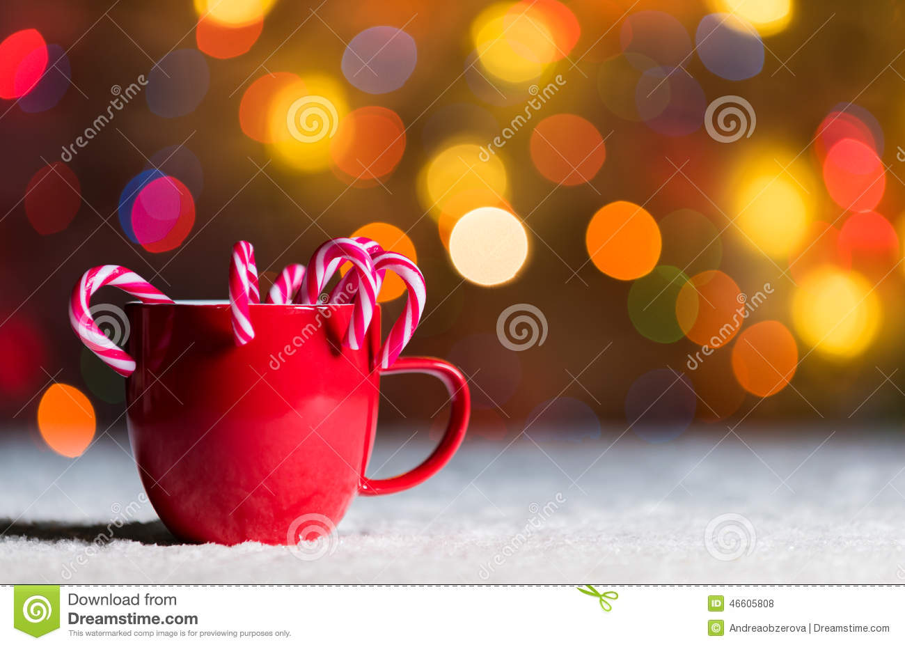 Red mug with candy canes in snow with defocussed fairy lights, bokeh in the background, Festive Christmas background