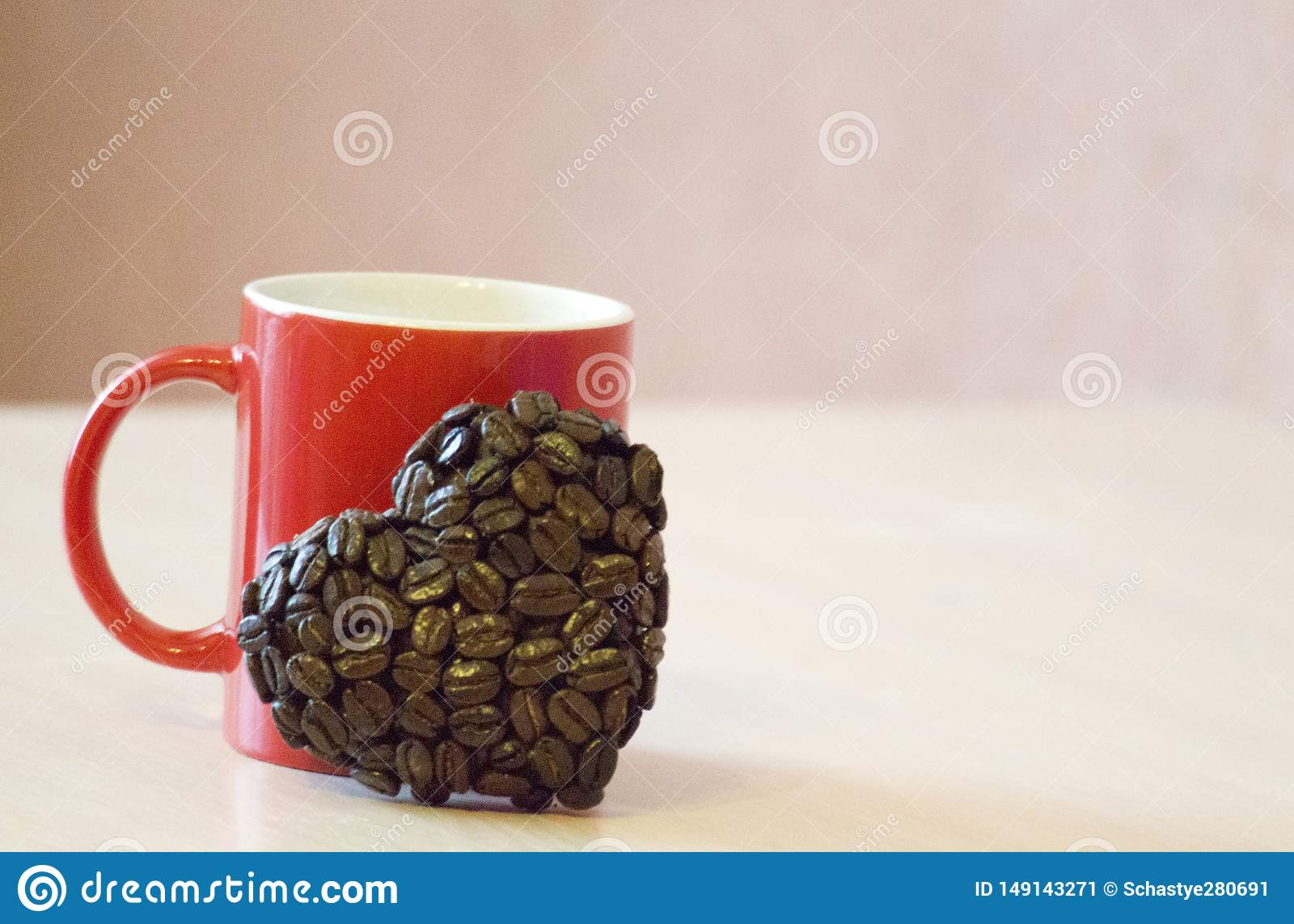 Red mug stands on the table, near the mug the heart shape of coffee beans, a symbol of love