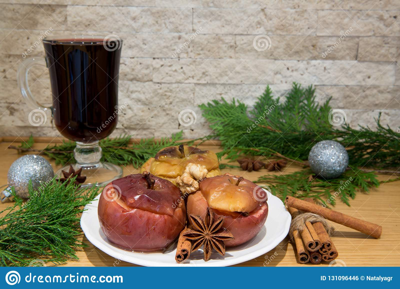 Red mulled wine and bake apples. Silver Christmas balls decoration.