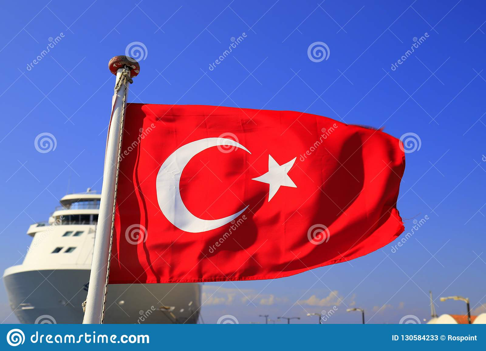 Red National Flag of Turkey with a half month and a star against the blue sky and a large white ocean liner, Turkish state symbol