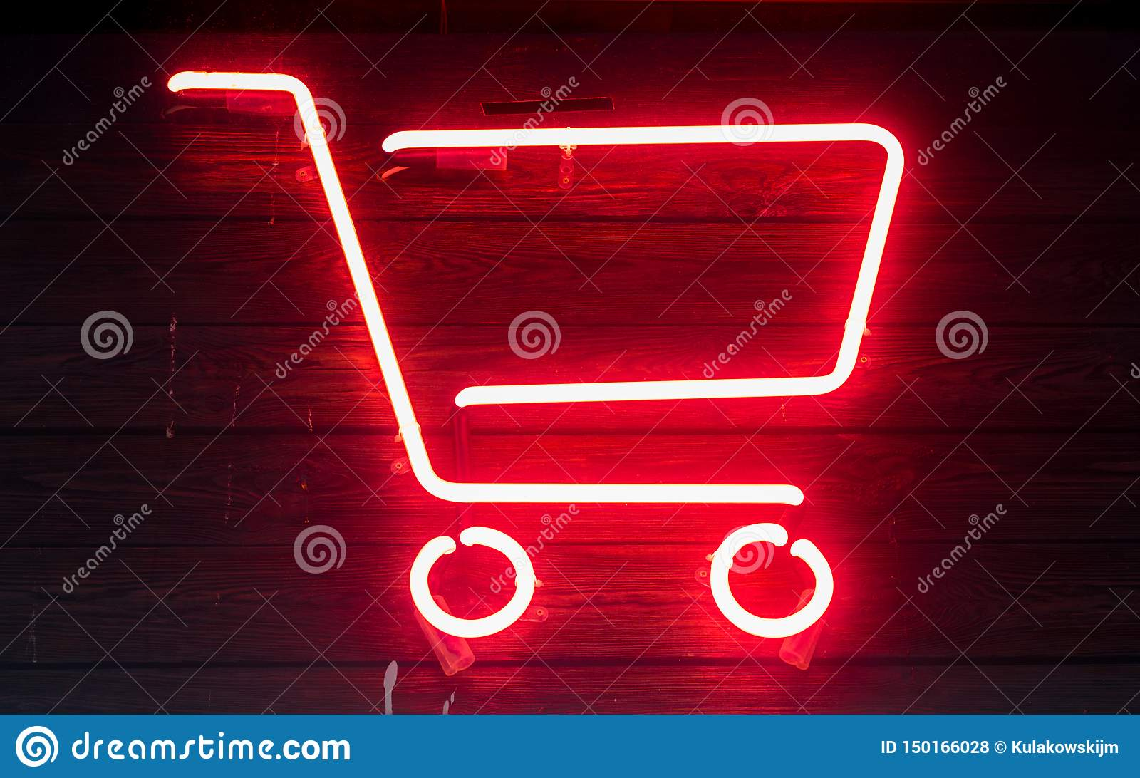 Red neon shopping cart on wooden surface