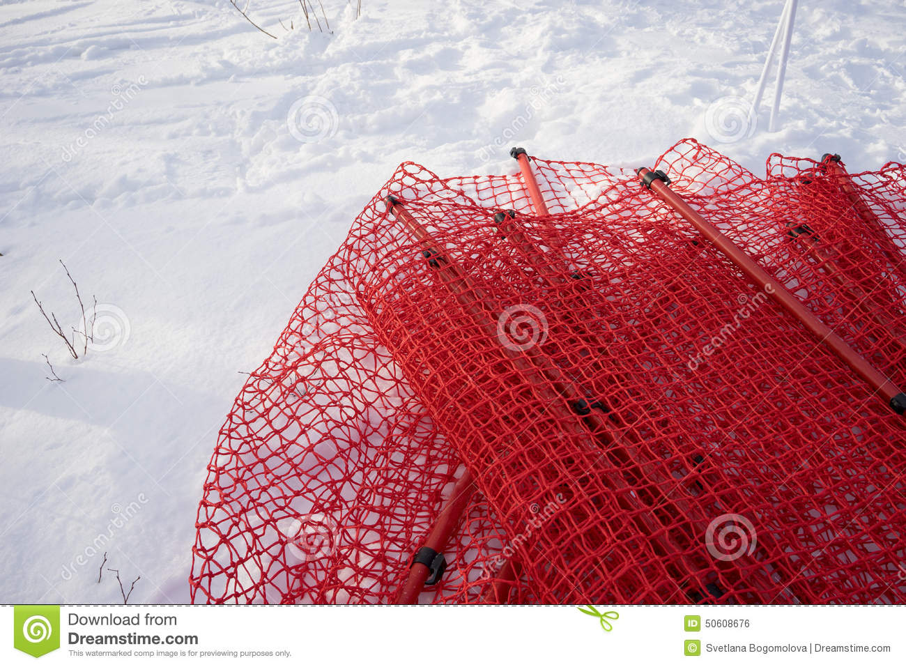 Red net hurdle laying on the snow stock photo image