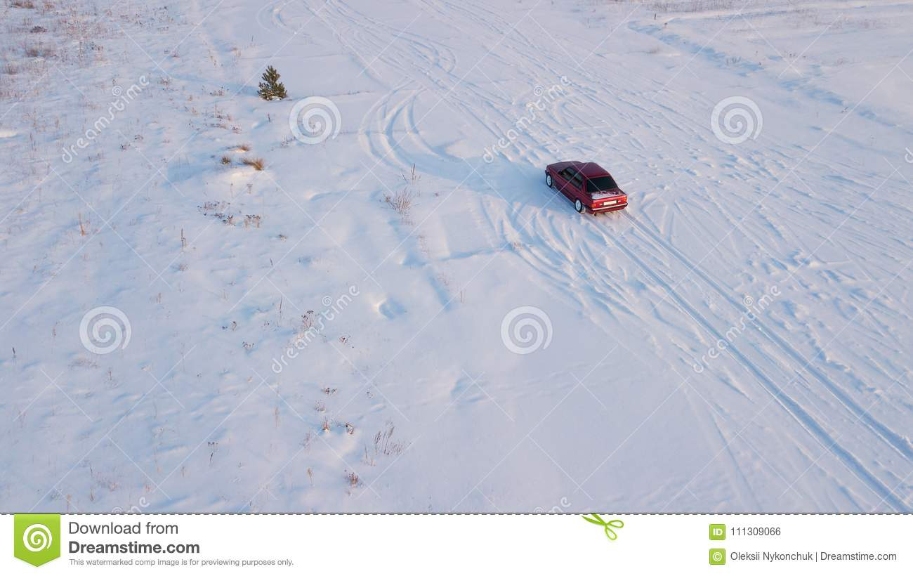 The Red Old Car Rides Along The Snow-covered Field Stock Photo ...