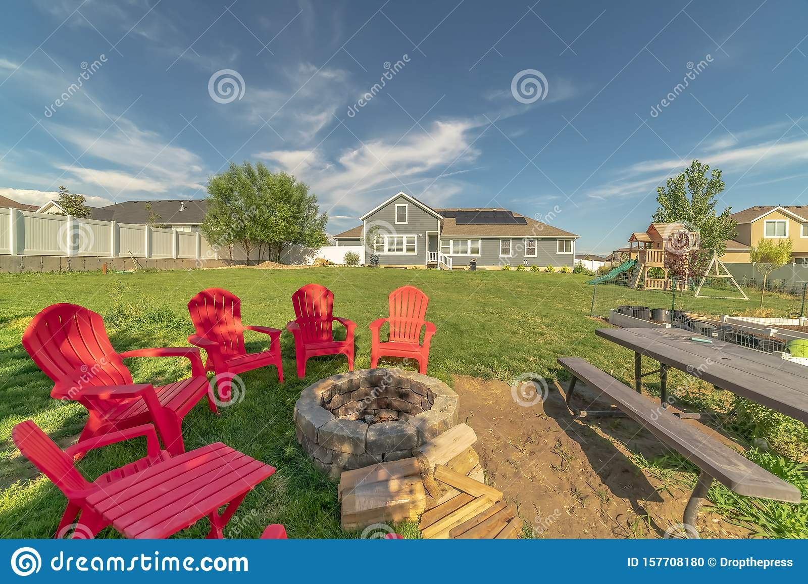 Red Outdoor Chairs And Picnic Table With Bench Around A Circular Stone Fire Pit Stock Photo Image Of Blue Sunny 157708180