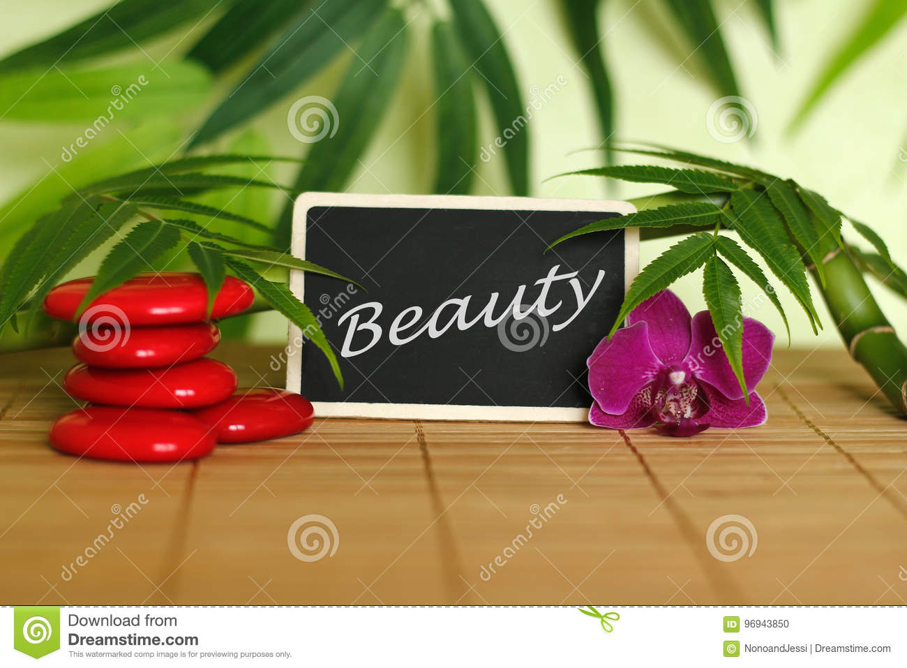 Red pebbles arranged in Zen lifestyle with an orchid, a lighted candle, a bamboo branch and foliage with the message beauty on the