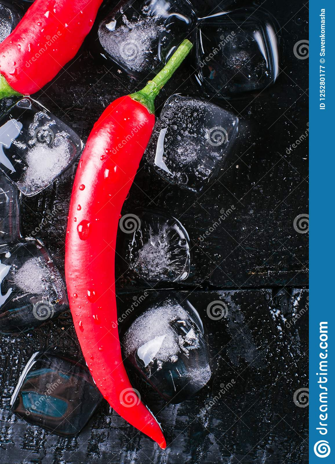 Red pepper and ice on a black wood background, fresh hot food on vintage table, freeze cold cube ice, mock up top view