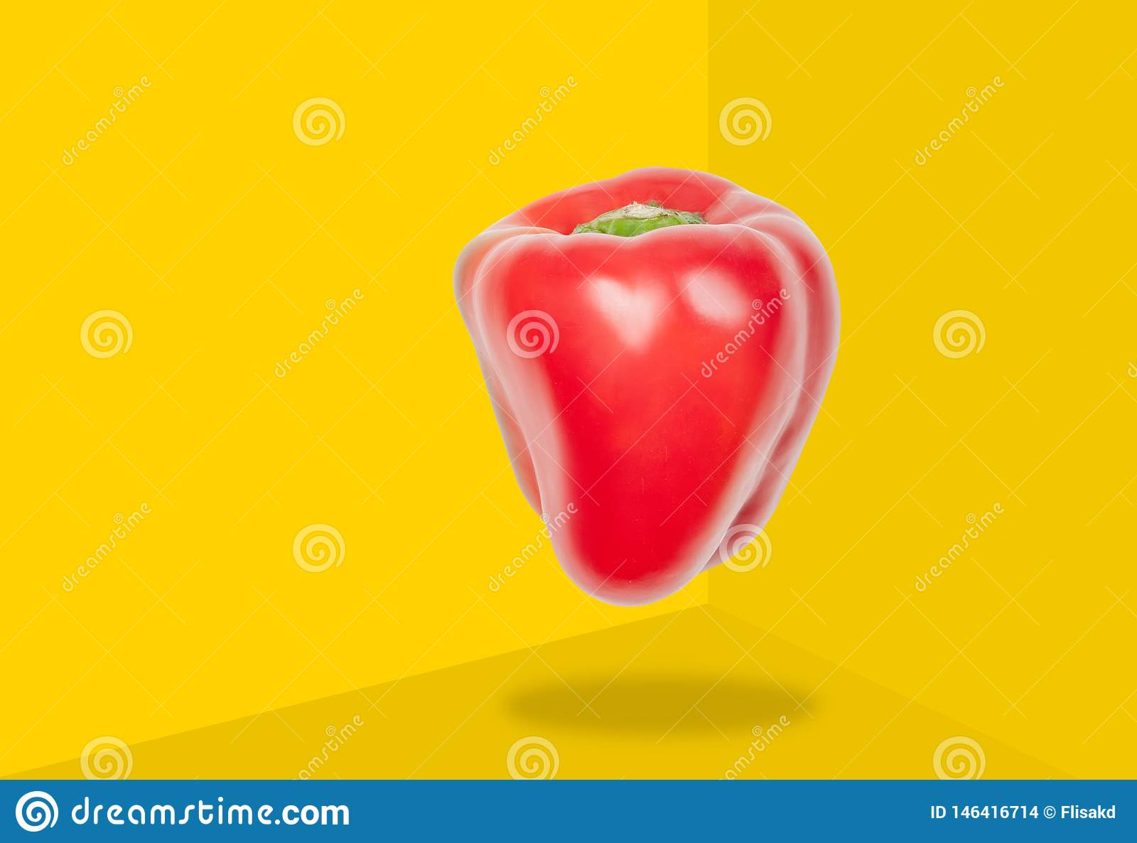Red pepper levitate in air on yellow background. Concept of vegetable levitation