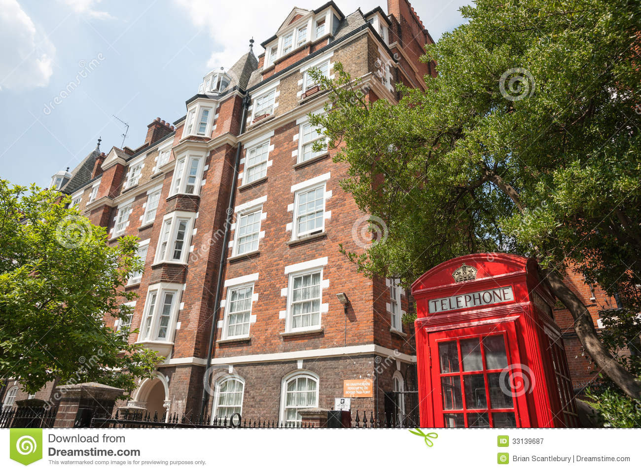 red phone box in front of red brick apartments royalty