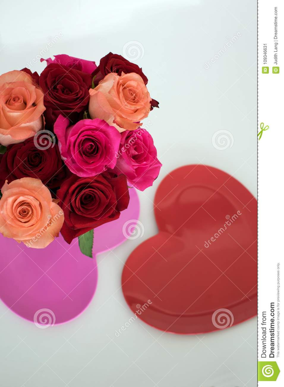 Red and pink roses arranged on top of pink heart shaped plate
