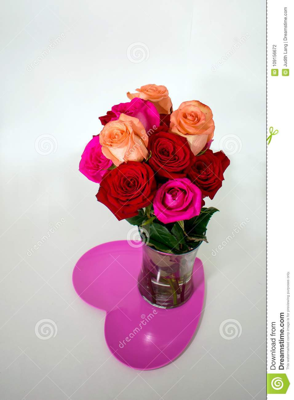 Red and pink roses in vase on top of pink heart