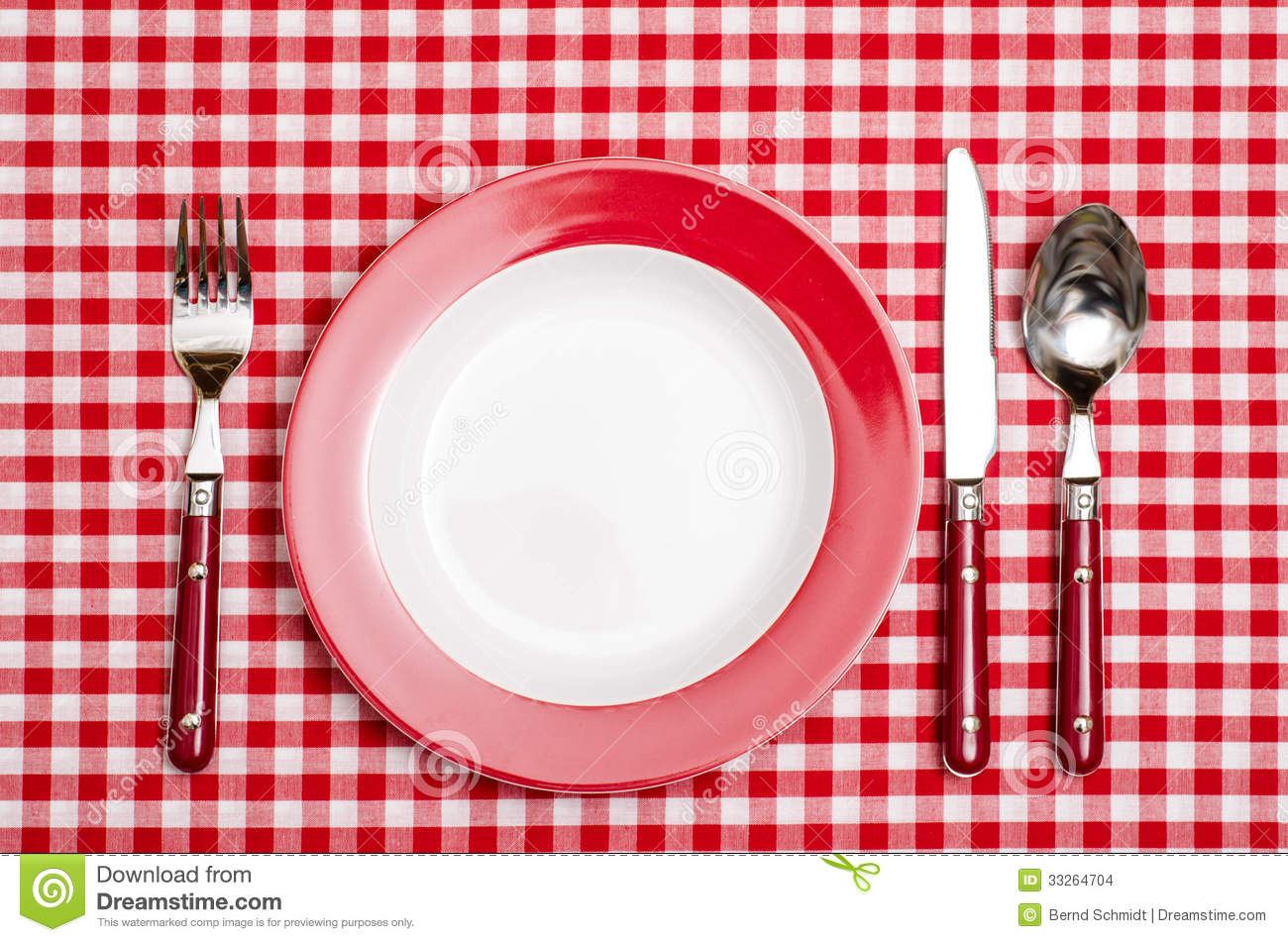Red place setting with red checkered table cloth in a restaurant.