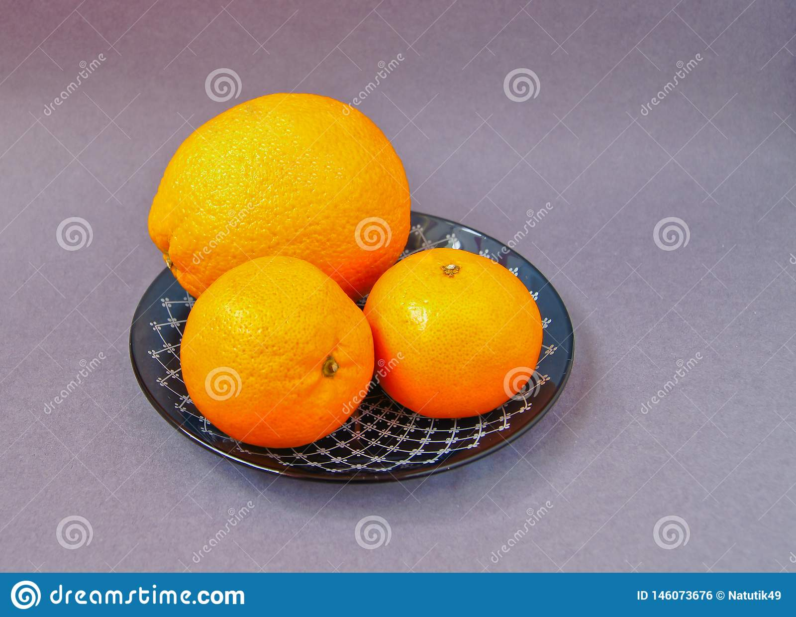 Red plate with oranges and tangerines green leaves bottle with juice on light background. Top view copy space