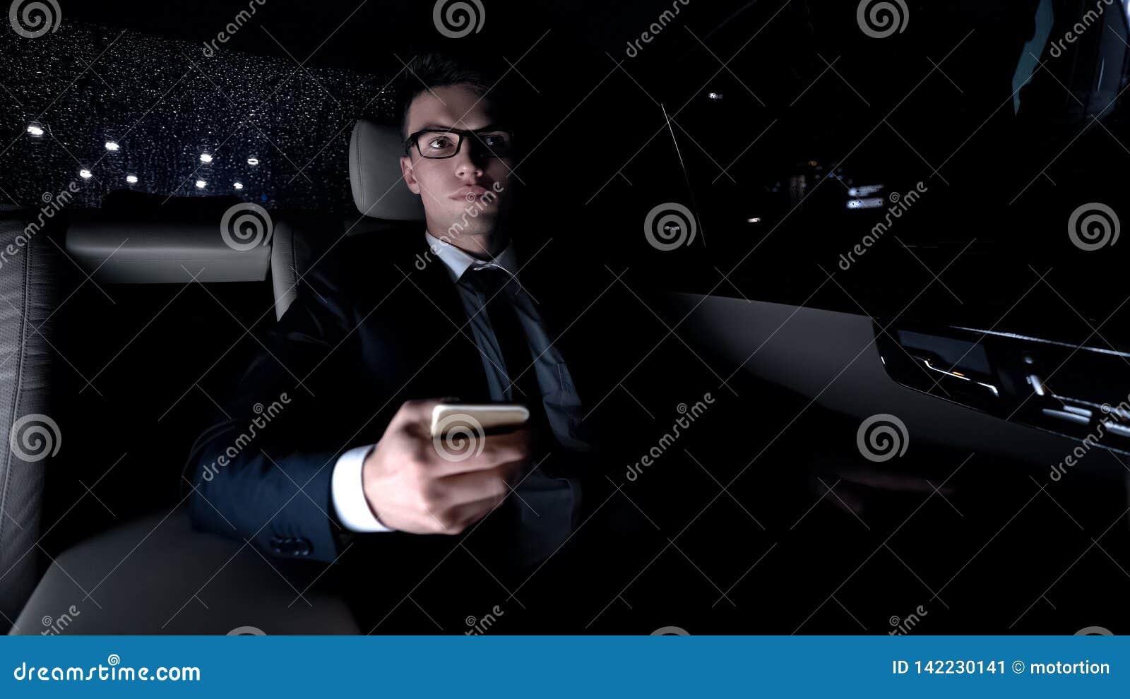 Red que practica surf del hombre de negocios cansado en smartphone, montando en el coche, analizando proyecto