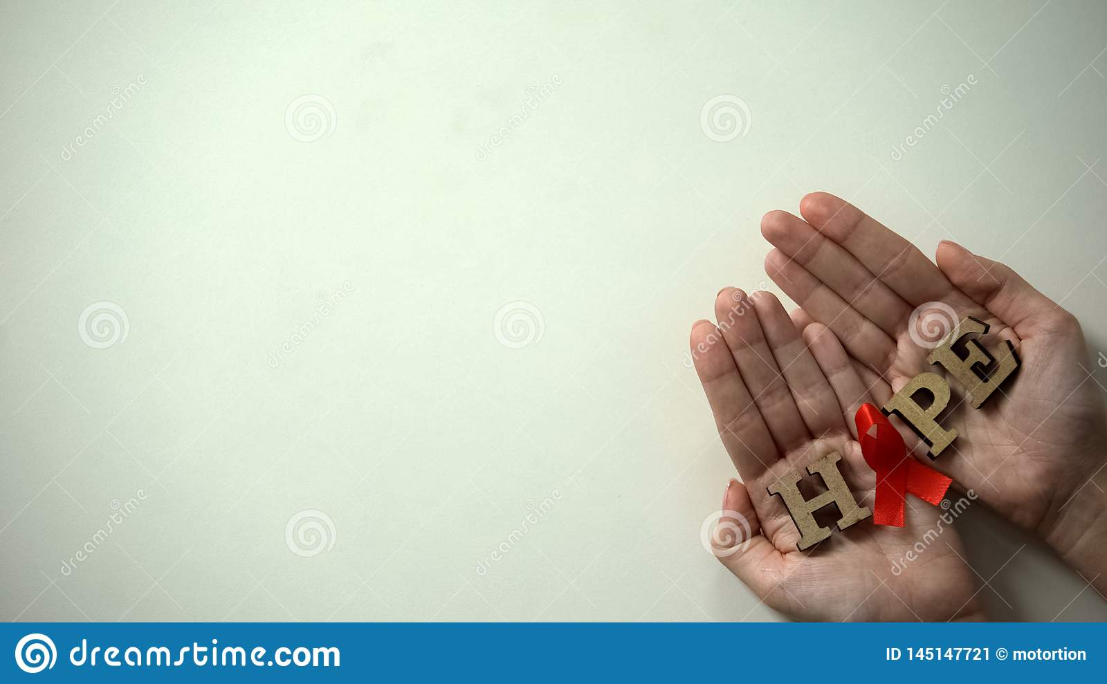 Red ribbon and hope word in female hands, AIDS awareness campaign, medication