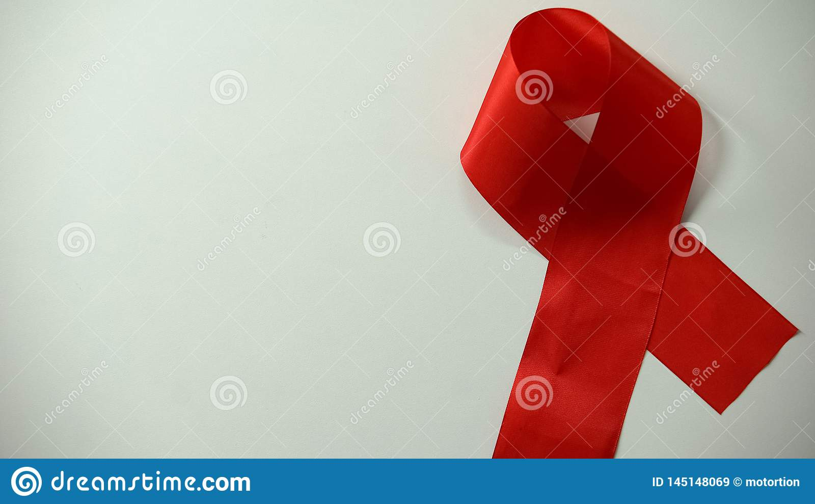 Red ribbon lying on table, AIDS awareness and prevention, healthcare, campaign