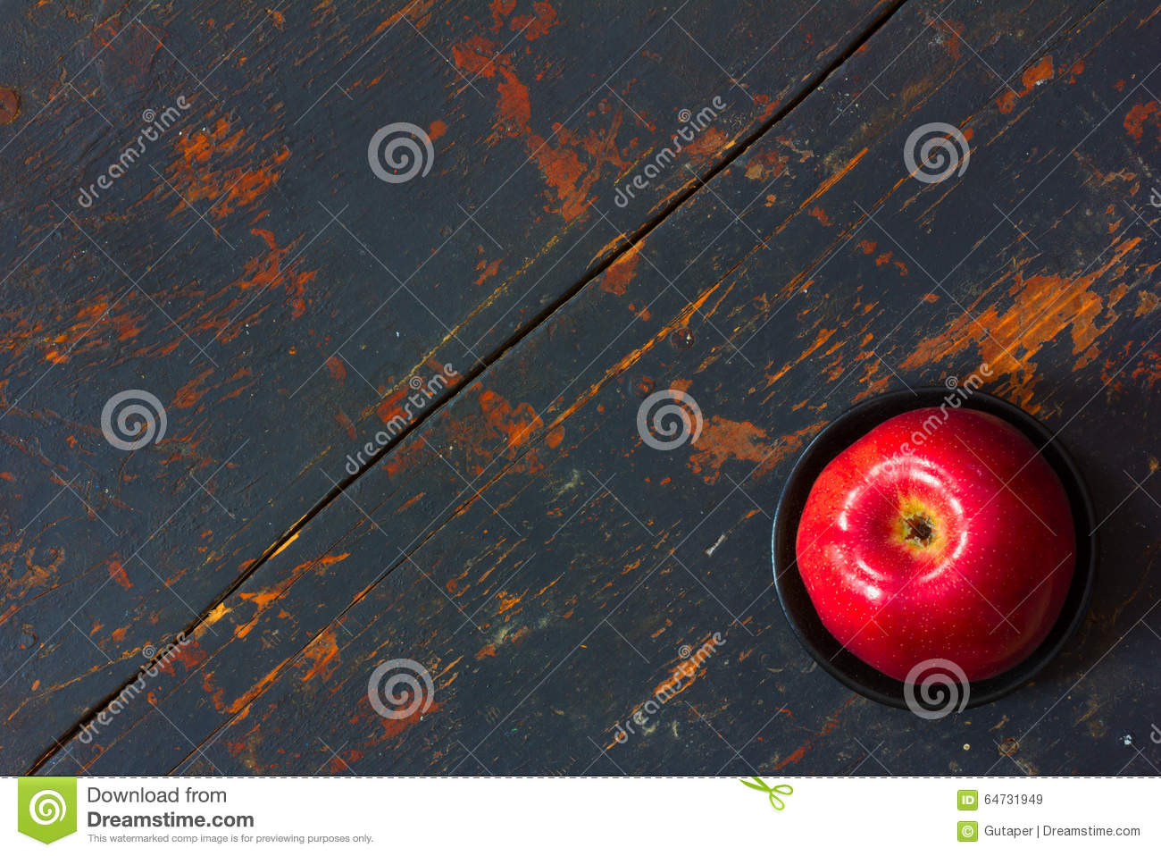 Red ripe apple in a black saucer on old background