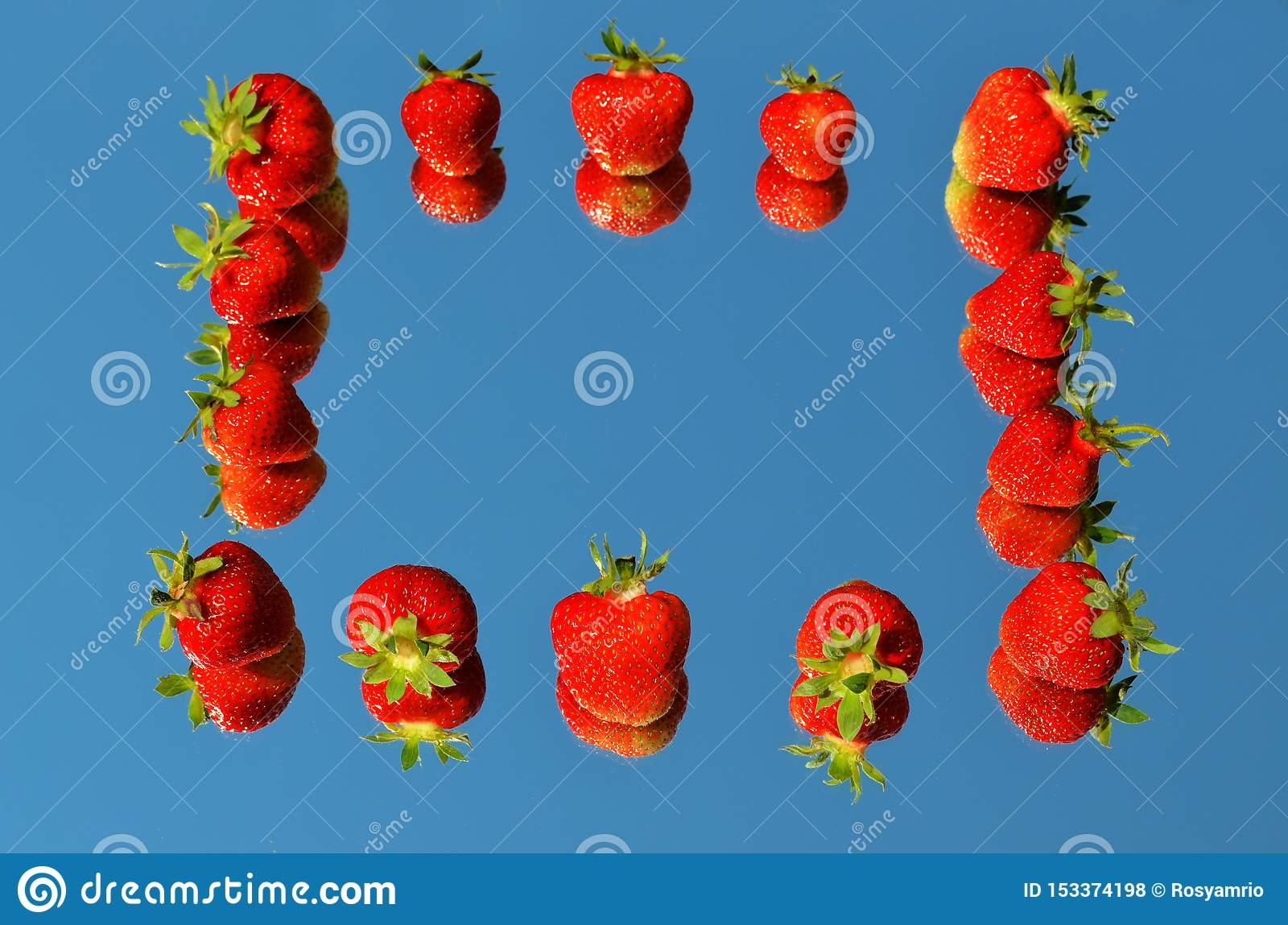 Red ripe strawberry berries laid on a mirror in the shape of a contour of a square with a reflection of the blue sky