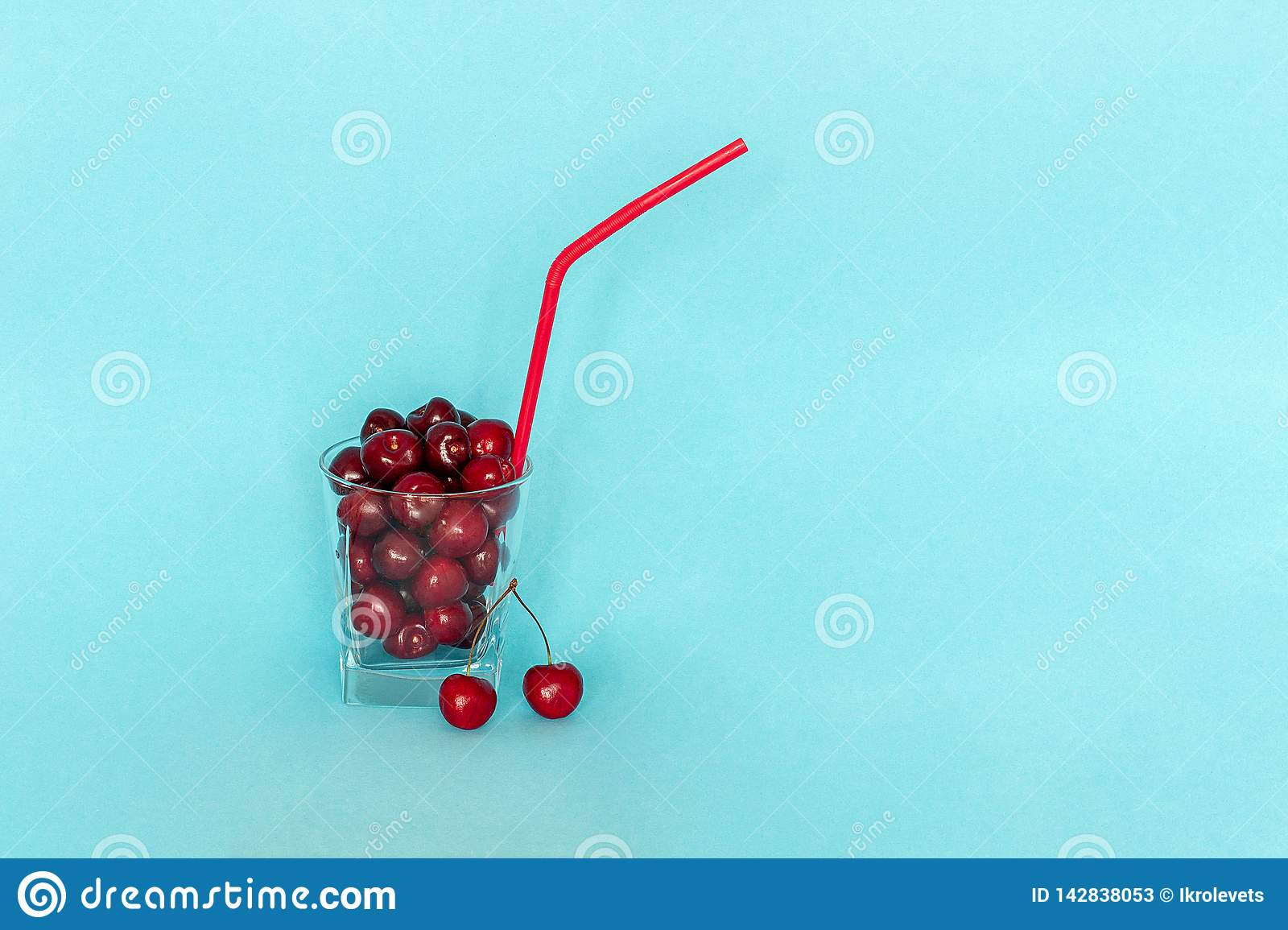 Red ripe sweet cherry in glass with straw on blue background. Concept of fresh natural juice, smoothies, healthy eating or diet