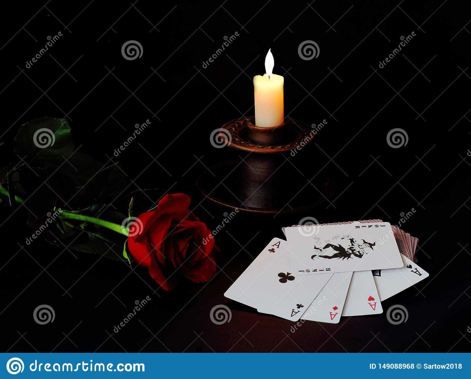 Red rose, ceramic candlestick with burning white wax candles and a deck of cards on a black background. Symbolic concept — life