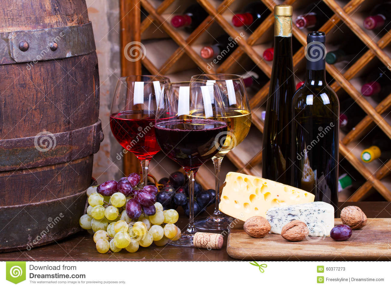 Red, rose and white glasses and bottles of wine. Grape, nuts, cheese and old wooden barrel.