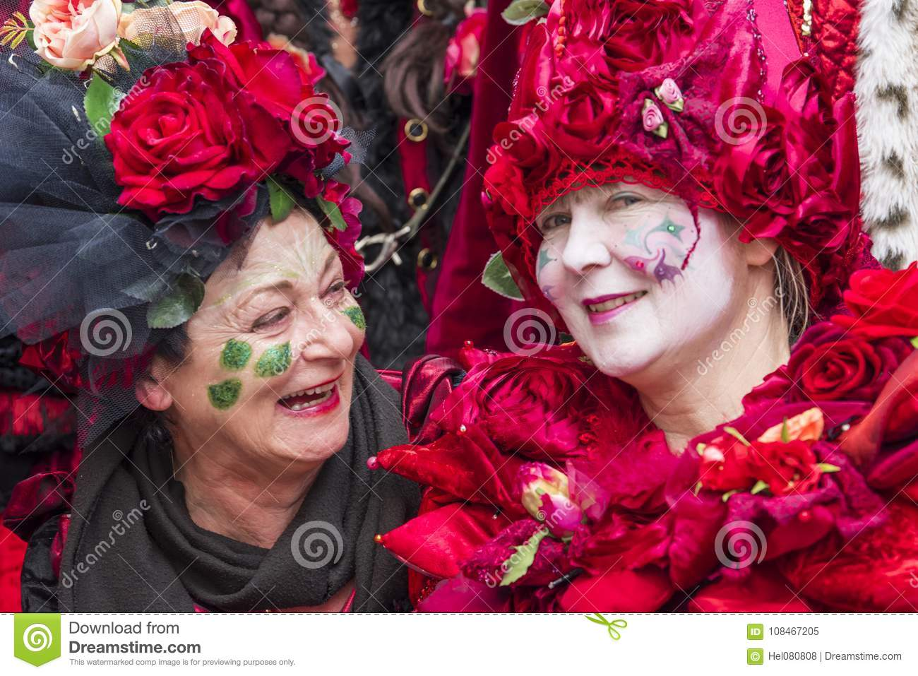 Beautiful costumed women with handmade rose dress at carnival in Zurich