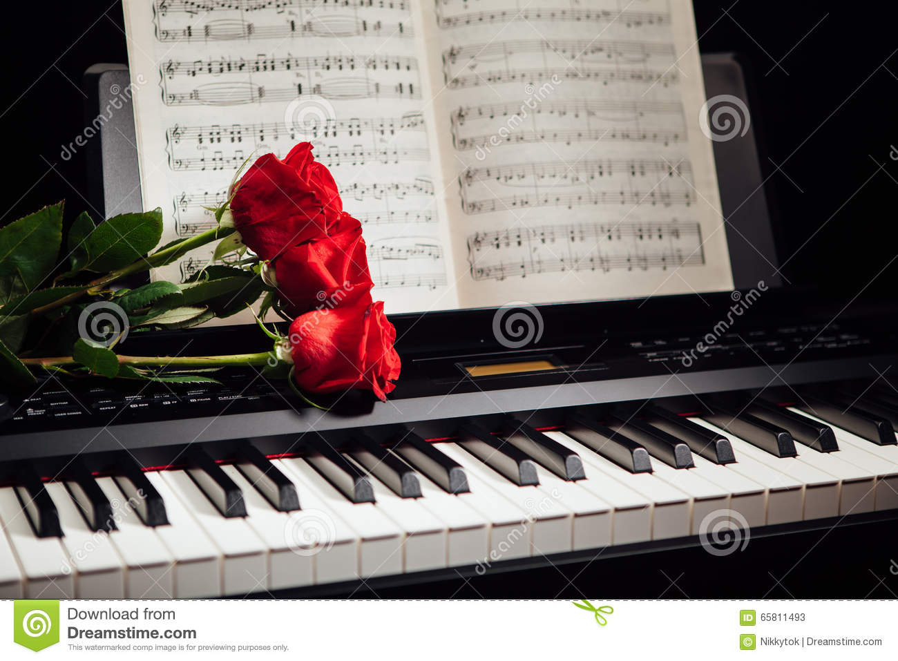 Red Roses On Piano Keys And Music Book Stock Photo