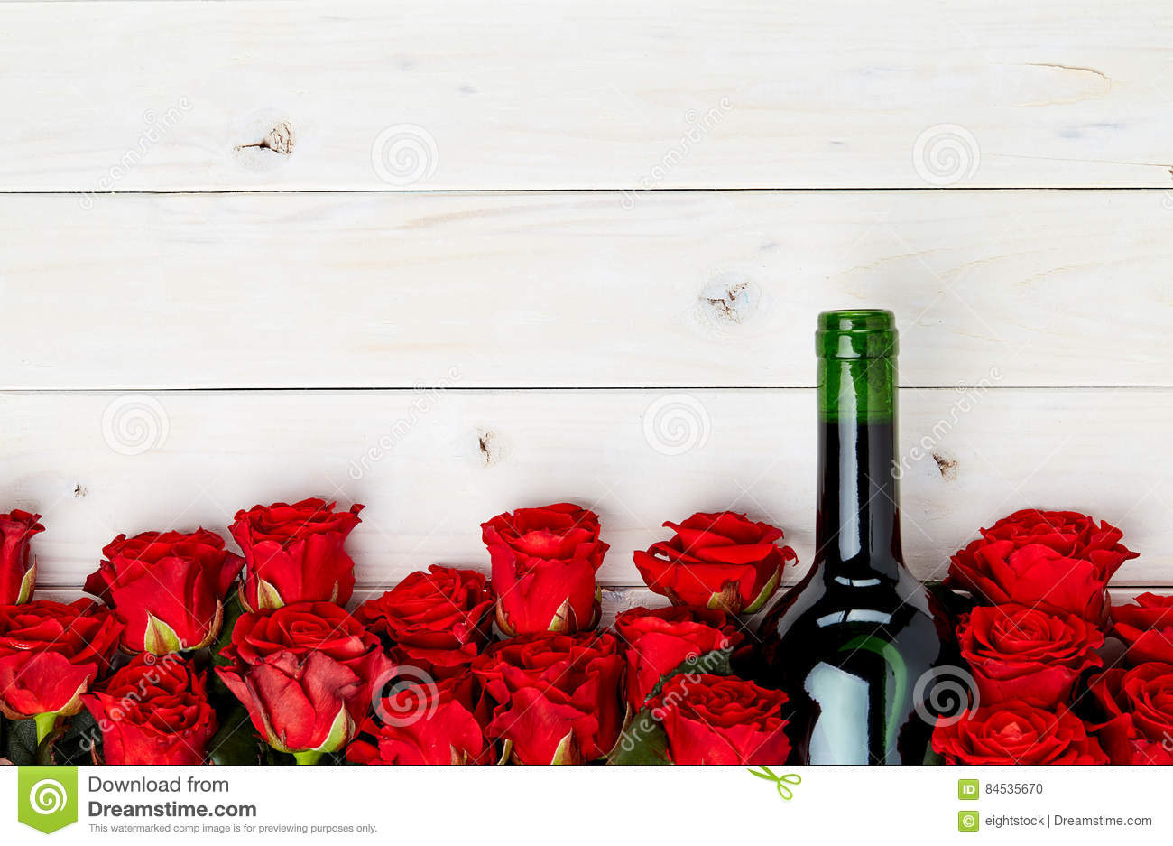 Red roses and wine on white background