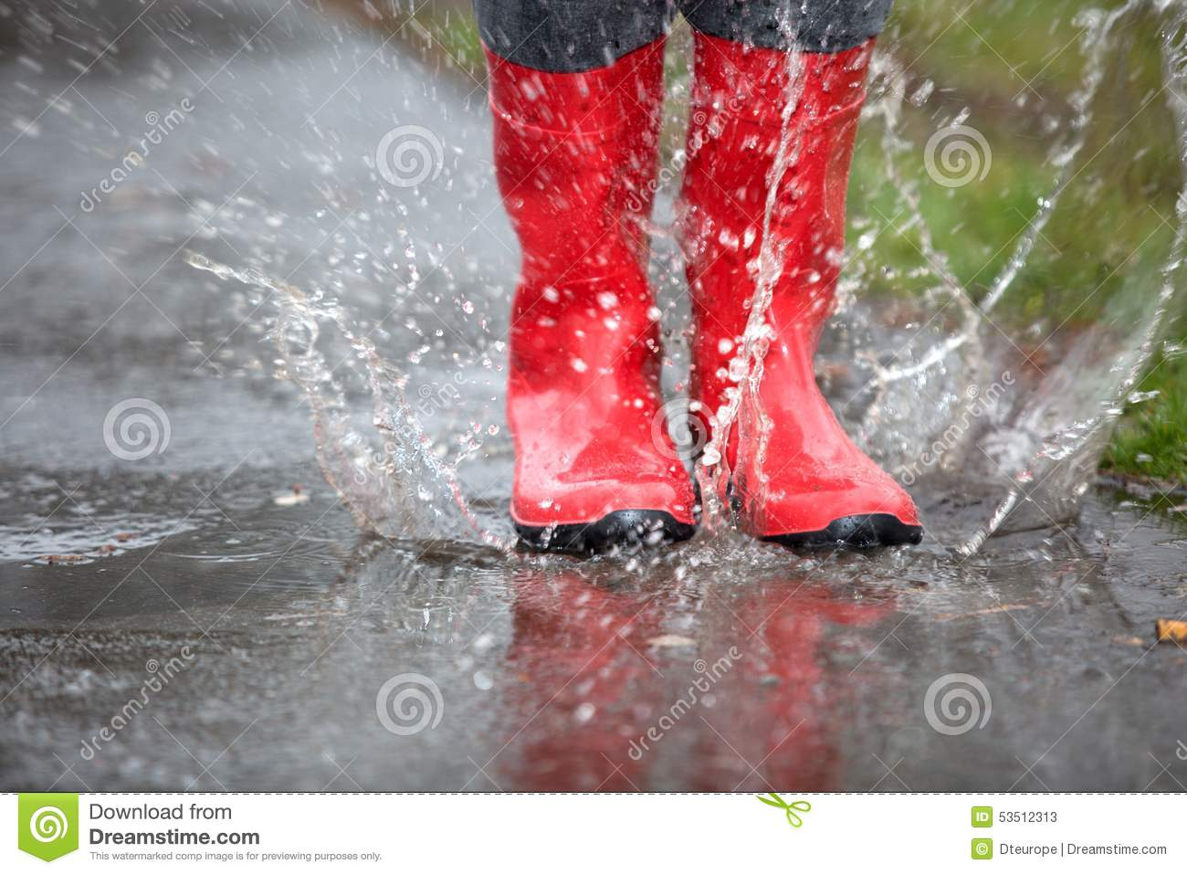 Red Rubber Boots Are Jumping Into A Big Puddle Stock Image