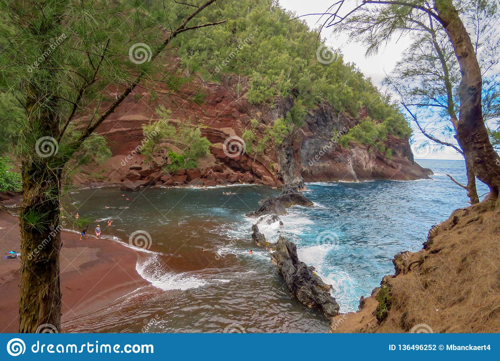 50b4d524cb Red sand beach or Kaihalulu Beach is a hidden cove with waves of the  pacific ocean breaking on the rocks near the shore line