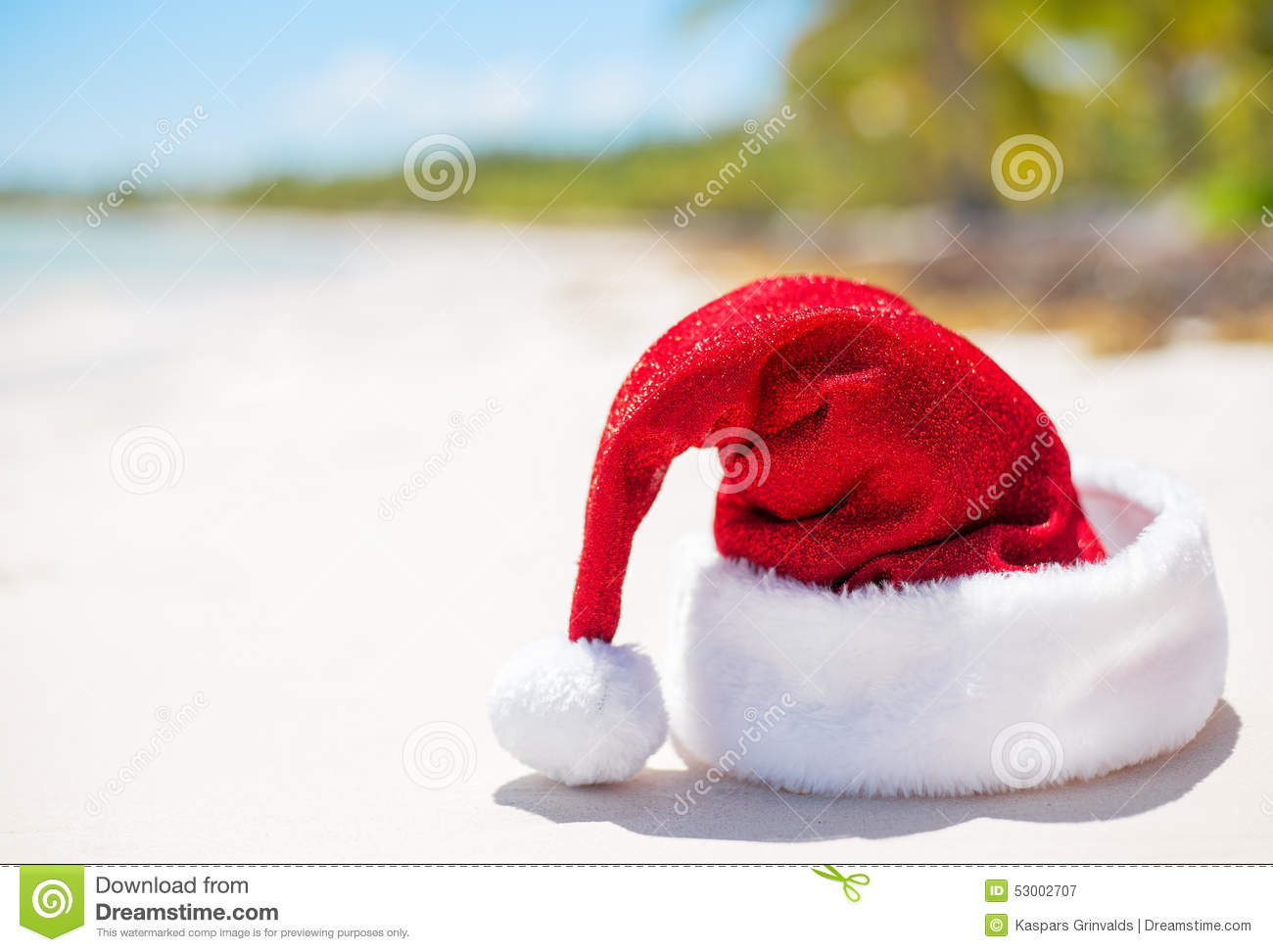Red Santa Claus hat on beach, theme for Christmas vacation and travel