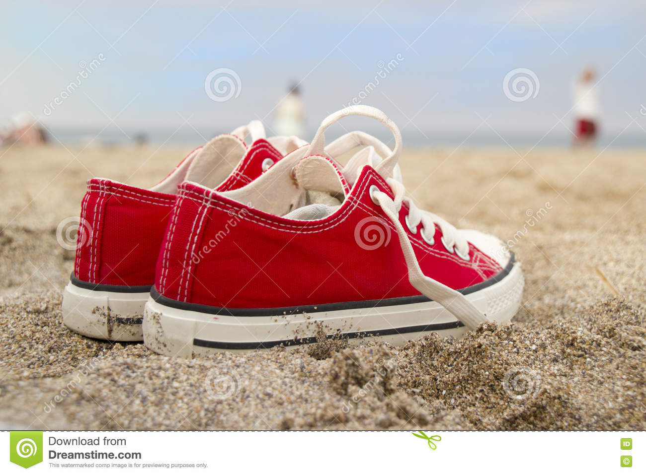 Red sneakers on sandy beach