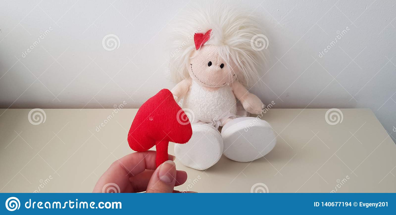 Red soft heart shape in female fingers